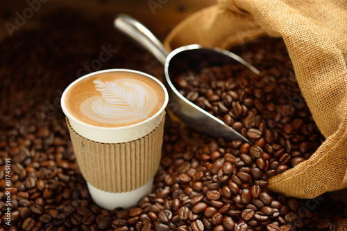 Paper cup of coffee latte and coffee beans on wooden table - 81745891
