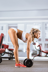 Woman in the gym with barbells