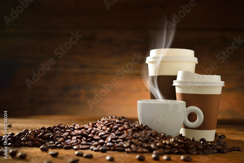 Cups of coffee and coffee beans on old wooden background - 81746004