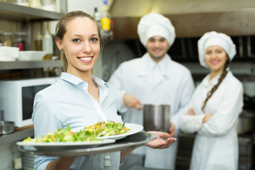 Chefs and waitress at kitchen