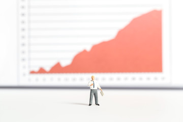 Business man standing in front of a graph.