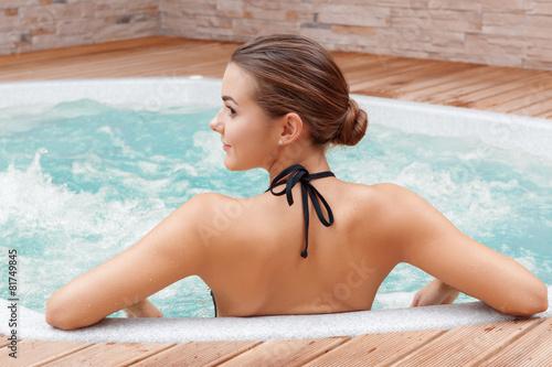 Leinwanddruck Bild Woman bathes in swimming pool