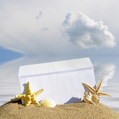 Seashells and starfish with blank letter on sand beach