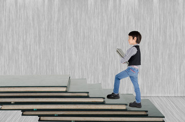 Little boy taking book go up book step