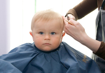 Serious 1-year boy during his first haircutting