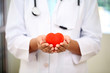 Female doctor holding a beautiful red heart shape - 81754401