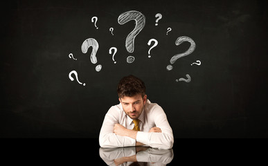 Sitting businessman under question marks