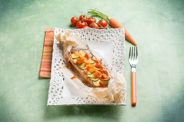 wrapped salmon with zuccinis tomatoes and carrots