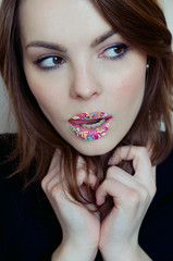 Beautiful woman with colorful candies on her lips.