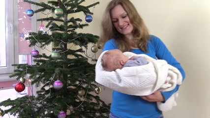 Happy mother sway newborn baby in hands near Christmas tree