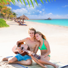 Blond tourist couple playing guitar at beach