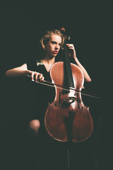 Attractive young woman playing the cello