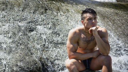 Attractive muscular shirtless young man under small waterfall