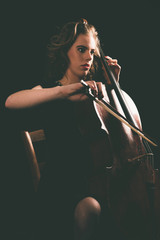 Sitting Young Woman Playing a Cello Instrument