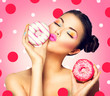 Beauty fashion model girl taking colorful donuts over pink