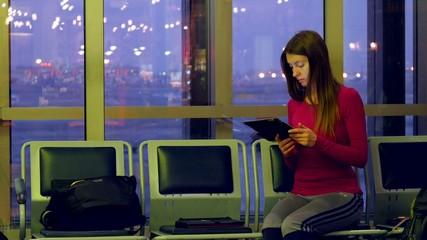 Young female passenger at the airport, using her tablet computer