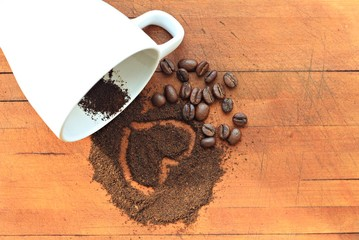 heart on coffee grounds and beans scattered sunlit background