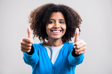 Young woman smiling and showing thumb-up