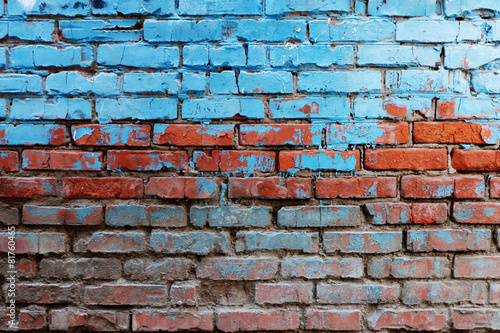 Wall Old red brick wall half painted in bright blue color a lot of