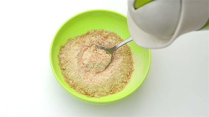 preparing instant oatmeal, pouring water and stirring by spoon