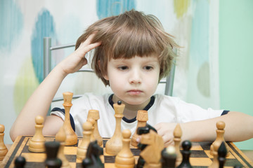 Young boy thinking on chess