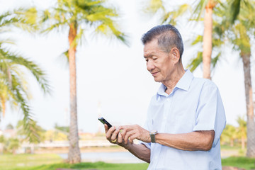 Asian senior man reading message on smartphone