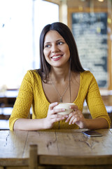Beautiful young woman sitting in a coffee shop and drink tea