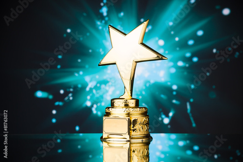 Leinwanddruck Bild gold star trophy against blue sparks background