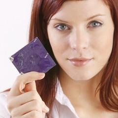 Junge Frau hält Kondom (Fokus auf Kondom)