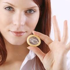 Frau hält Kondom zwischen ihren Fingern