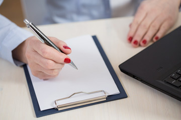 Woman writes in a notebook