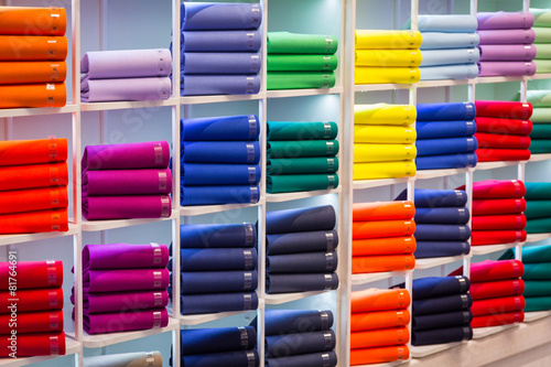 Colorful sweaters on the shop shelfs - 81764691
