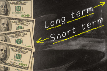 Text on blackboard with money - Long term and short term