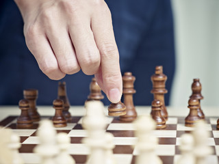 hand of a man moving a pawn to start a chess match