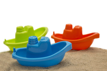 Three plastic toy boat on sand isolated on white