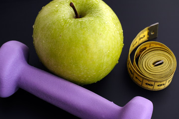 Dumbbell and green apple with tape measure