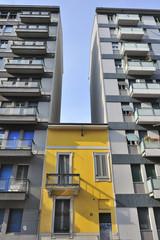 Milano piccola casa gialla tra alti palazzi