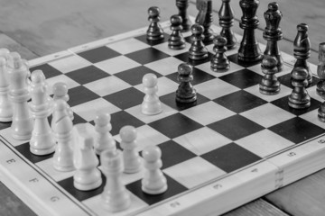 Wooden chess set fight, black and white photo.