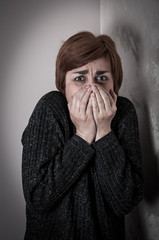 Scared and abused woman covering her mouth with her hands