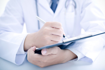 Close-up Of Male Doctor Filling The Medical Form