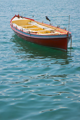 Wooden red boat in a calm lake