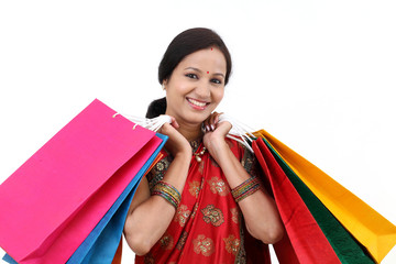 Cheerful traditional Indian woman with shopping bags