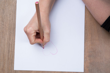 Hand of a woman drawing a pink heart