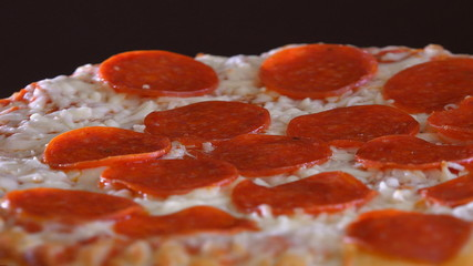 Italian Cuisine: Pepperoni Pizza Slowly Turning in Display