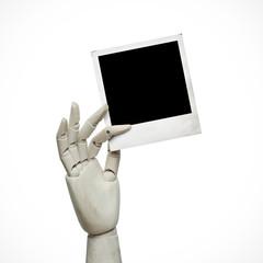 White wood hand with polaroid frame