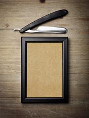 Straight razor and kraft poster on wood desk
