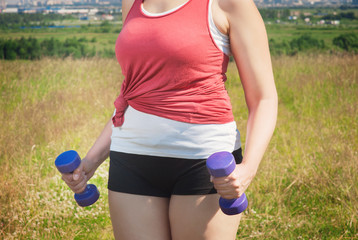 Plus size woman exercising with dumbbells