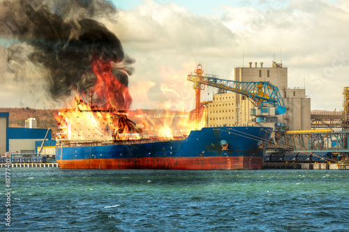 Burning cargo ship in the port. - 81777410