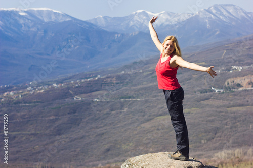 Poster girl standing with hands-up on a cliff in the mountains  and
