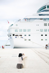 Passenger photographing big cruise ship